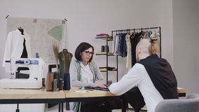 Couple of fashion designers are working in workshop. Attractive young woman in glasses and stylish bearded man are in stock video footage