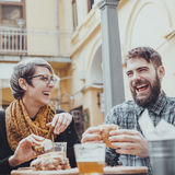 Couple In Fast Food Restaurant. Cheerful Couple In Fast Food Rastaurant Eating Burgers Royalty Free Stock Images