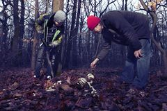 Human skeleton found in winter forest by couple of man royalty free stock photo