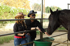 Couple feeding a black horse Royalty Free Stock Images