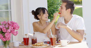 Couple feeding each other at breakfast Royalty Free Stock Photography