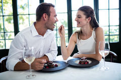 Couple feeding each other and smiling Stock Photography