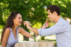 Couple feeding strawberries to each other at outdoor café Stock Photo