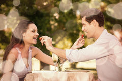Couple feeding strawberries to each other at outdoor café Stock Image