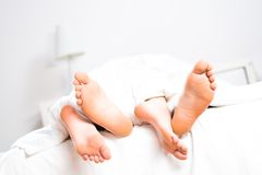 Couple feet in bed Stock Photography