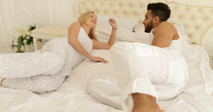 Couple feet run jump on bed mix race man woman embrace bedroom