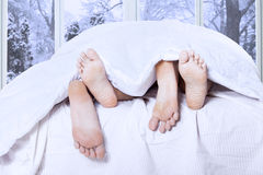 Couple feet sleeping on bed Stock Photography