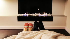 Couple Feet in Socks by Fireplace. Man and Woman Relaxing by Warm Fire and Warming Up Their Feet. Family in Winter or Autumn Concept. Modern Ethanol Fireplace stock video