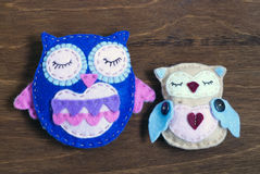 Couple of felt owls on a wooden background Stock Photo