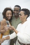 Couple With Female Friend Reading Text Message Stock Images