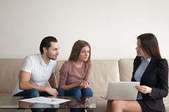 Couple with female real estate agent discussing renting buying a Royalty Free Stock Photos