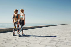 Couple female running exercising jogging happy on waterfront. Training as part of healthy lifestyle. Two back young fit girls runners Royalty Free Stock Photography
