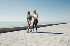 Couple female running exercising jogging happy on waterfront royalty free stock images