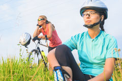 A couple of female sport athletes resting together outdoors. Stock Image