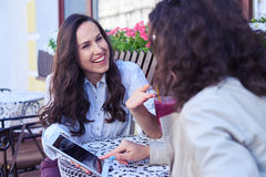 Couple of females discussing and looking photos at tablet Stock Photos