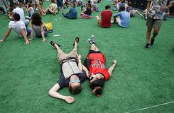 Couple of festival goers laying on ground enjoying sonar festival. Festival goers seen laying on the ground during live events performances at Sonar Advanced stock photography