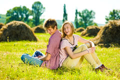 Couple in field. Couple sitting in field of haystacks stock images