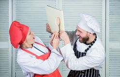 Couple fight for book recipes. Improve cooking skill. Book recipes. Helpful culinary book. Woman chef and man cooking royalty free stock images