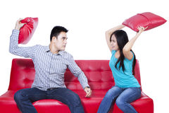 Couple fight on red sofa - isolated Stock Photography