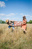 Couple fighting in field hoding suitcase on countryside landscape blue sky background outdoors. Couple fighting in field hoding suitcase on countryside landscape royalty free stock photography
