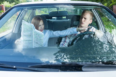 Couple fighting over driving directions. Young couple arguing in a car with a map Stock Photo