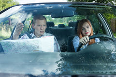 Couple fighting over driving directions. Young men and women arguing over travel directions Stock Images