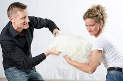 Couple is fighting for pillow Royalty Free Stock Images