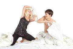 Couple fighting with pillows in bed Royalty Free Stock Image