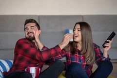 Couple fighting for remote control while watching TV at home stock photography