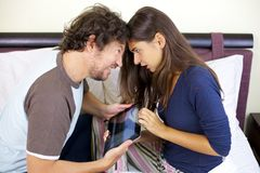 Couple fighting for tablet in bed stock photography