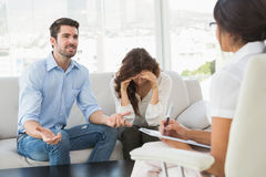 Couple fighting together in front of their therapist Royalty Free Stock Photos