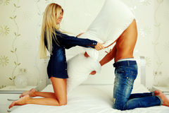 Couple fighting together with pillows Stock Photography