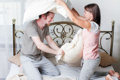 Couple fighting together with pillows in bed Royalty Free Stock Photos
