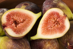 Couple of figs in a pot over a wooden table Royalty Free Stock Images