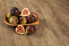 Couple of figs in a pot over a wooden table Royalty Free Stock Photography