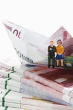 Couple figurine on bundles of euro notes with paper boat Stock Photography