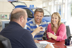 Couple filling in paperwork in car showroom Royalty Free Stock Photography