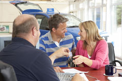 Couple filling in paperwork in car showroom Royalty Free Stock Photos