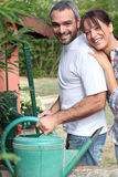 Couple filling up watering can Stock Photos