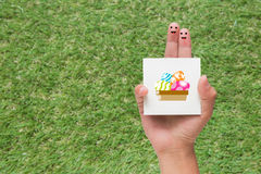 Couple of fingers with painted smiley holding easter note. On grass background stock images