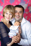 Couple with first new baby. Portrait of a couple with  newborn baby Stock Image