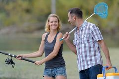 Couple fishing or angling standing on river shore in grass. Couple stock photography