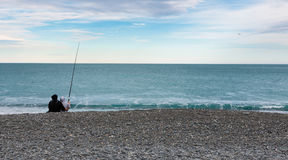 Couple fishing on ocean shore Stock Photos