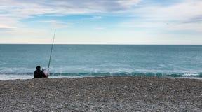 Couple fishing on ocean shore Stock Photos