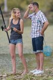 Couple fishing in pond using fishing rod Stock Images