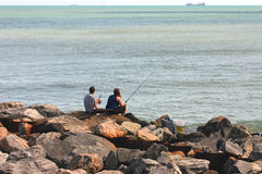 Couple fishing on rocks. Couple fishing on rocky jetty by the ocean Royalty Free Stock Image