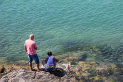 Couple fishing in the sea stones Royalty Free Stock Photo