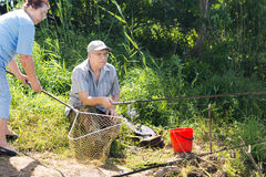 Couple fishing with the woman holding a net Royalty Free Stock Photography
