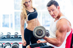 Couple in fitness gym with dumbbells lifting weight. As sport, men and women training together Royalty Free Stock Photos