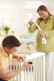 Couple fixing baby bed together Stock Photography